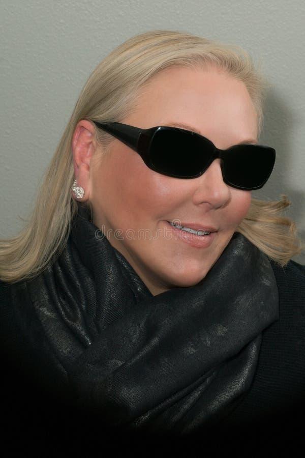Le för halsduk och för solglasögon för blond kvinna bärande arkivbild