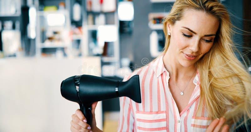 Le för slaguttorkning för ung kvinna hår fotografering för bildbyråer