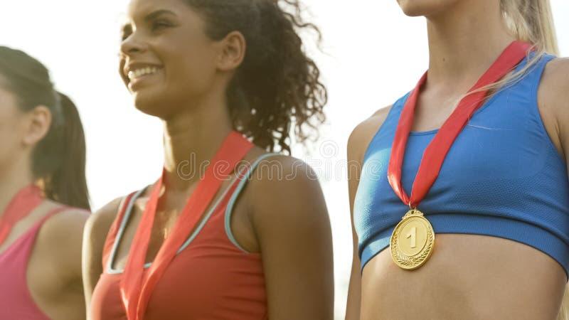 Le för sportflickor som står med medaljer på podiet som är stolt av prestationer fotografering för bildbyråer