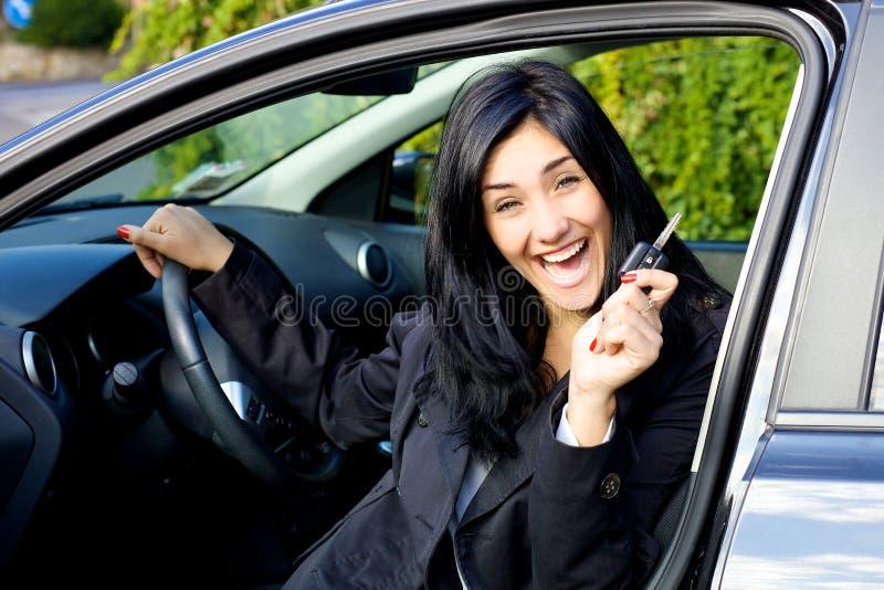 Le för ung kvinna som är lyckligt om den nya bilen fotografering för bildbyråer