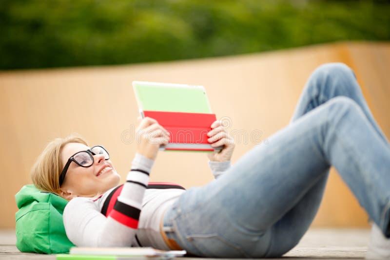Le för ung kvinna som ligger på träplattformen arkivfoton
