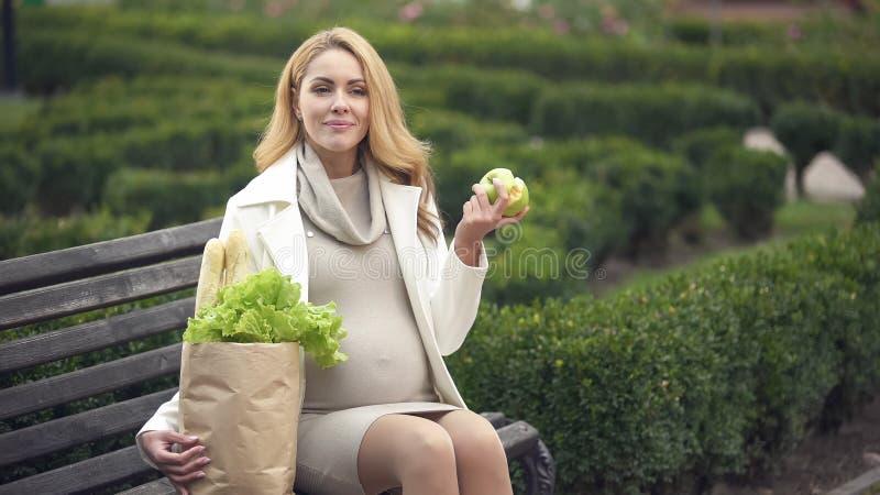 Le förvänta damen som äter det nya äpplet på bänk med livsmedelsbutikpåsen, hälsovård royaltyfri foto