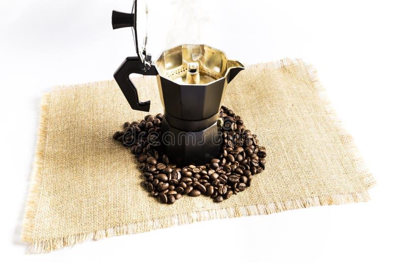 Le fabricant de café italien avec du café chaud a juste fait à côté de beaucoup de grains de café photographie stock libre de droits