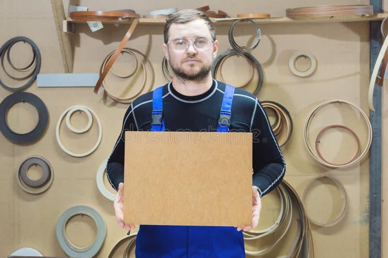 Le fabricant des meubles dans les vêtements et les lunettes spéciaux garde un plat vide pour le texte tandis que sur leur lieu de image stock