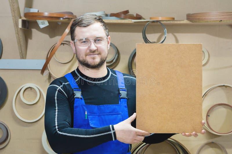 Le fabricant des meubles dans les vêtements et les lunettes spéciaux garde un plat vide pour le texte tandis que sur leur lieu de photographie stock libre de droits