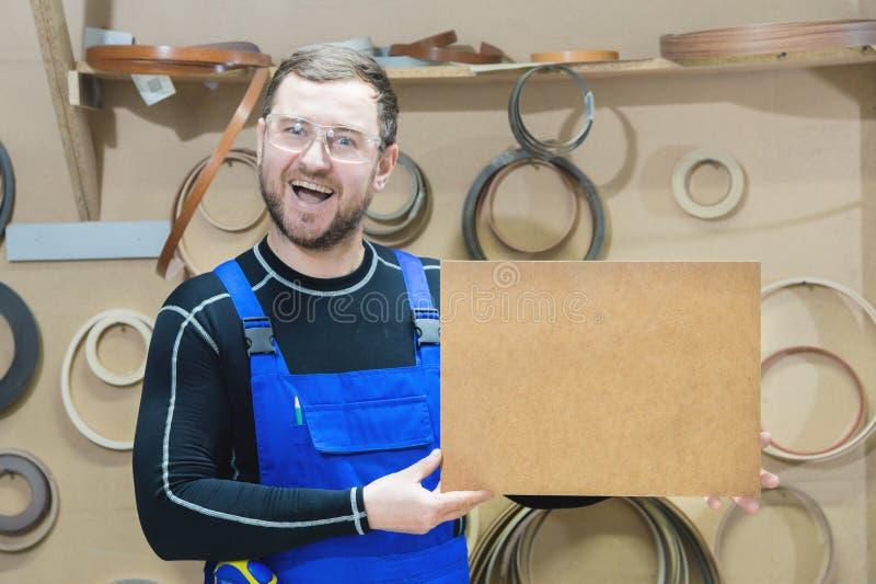 Le fabricant des meubles dans les vêtements et les lunettes spéciaux garde un plat vide pour le texte tandis que sur leur lieu de photo libre de droits
