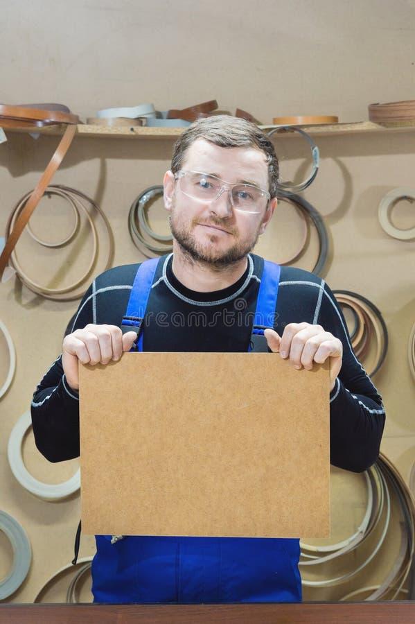 Le fabricant des meubles dans les vêtements et les lunettes spéciaux garde un plat vide pour le texte tandis que sur leur lieu de photographie stock