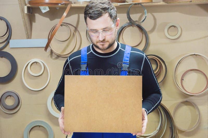Le fabricant des meubles dans les vêtements et les lunettes spéciaux garde un plat vide pour le texte tandis que sur leur lieu de images stock