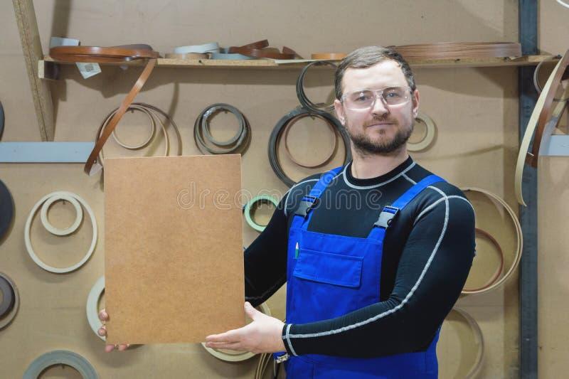 Le fabricant des meubles dans les vêtements et les lunettes spéciaux garde un plat vide pour le texte tandis que sur leur lieu de photos stock