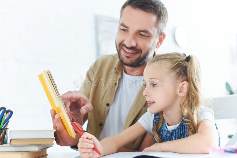 le fadern och den lilla dottern som tillsammans gör läxa arkivfoto