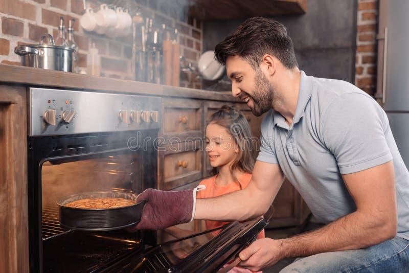 Le fadern och dottern som tar kakan från ugnen arkivbild