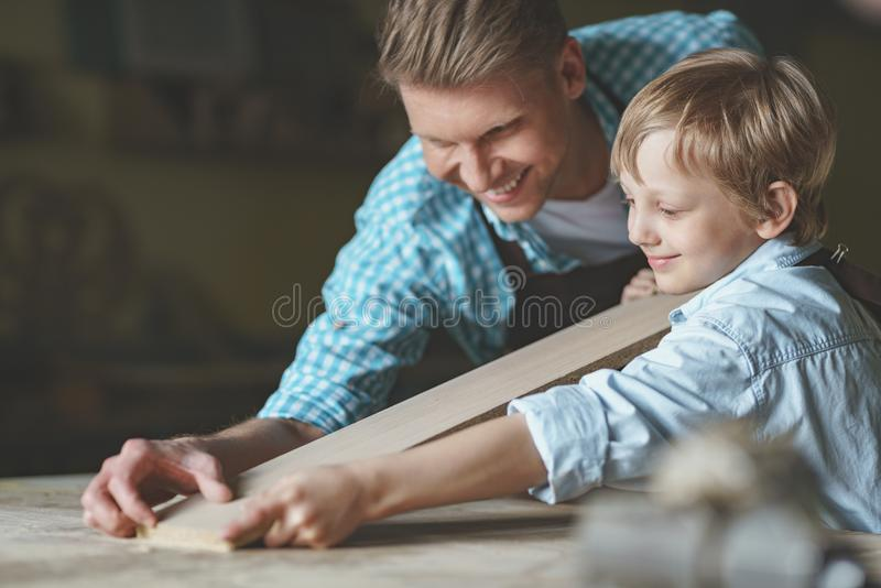 Le fadern och sonen med ett bräde royaltyfri foto