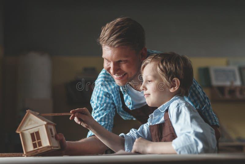 Le fadern och sonen med ett trähus royaltyfri bild