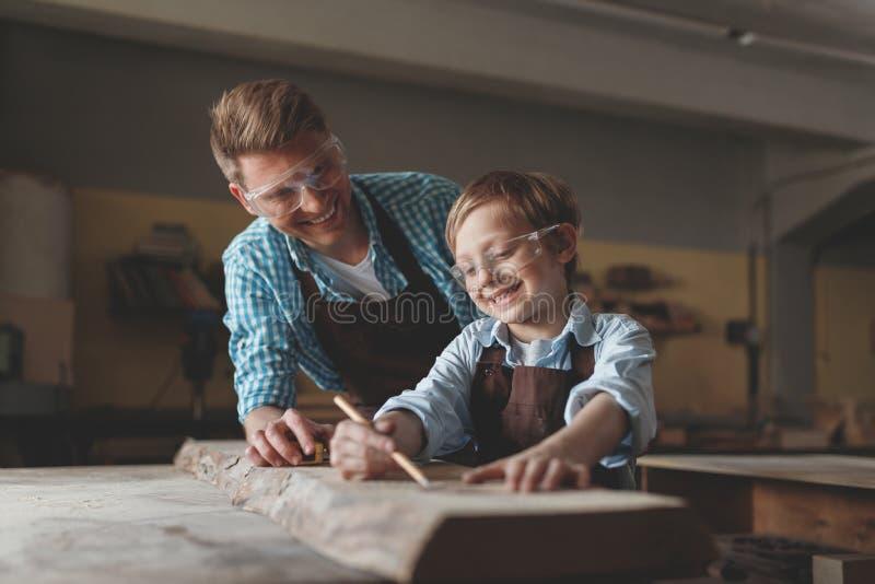 Le fadern och sonen med exponeringsglas på arbete arkivfoto