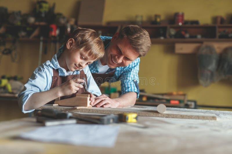Le fadern och sonen på arbete royaltyfria foton