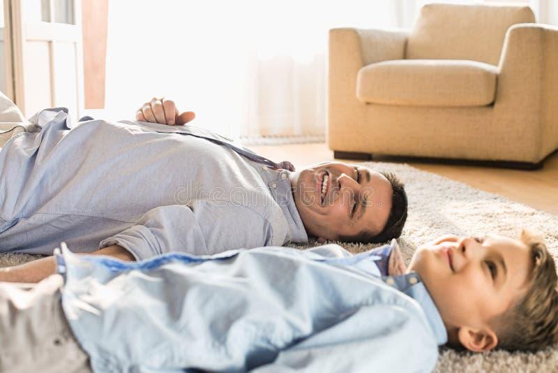 Le fadern och sonen som hemma kopplar av på golv arkivbilder