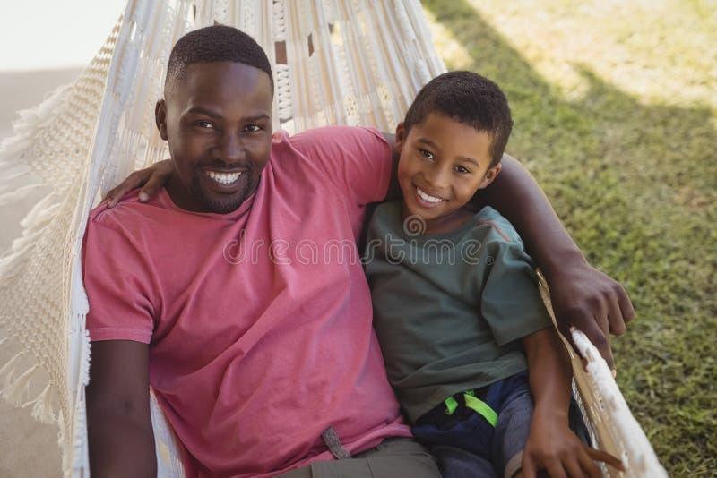 Le fadern och sonen som kopplar av på en hängmatta royaltyfri foto