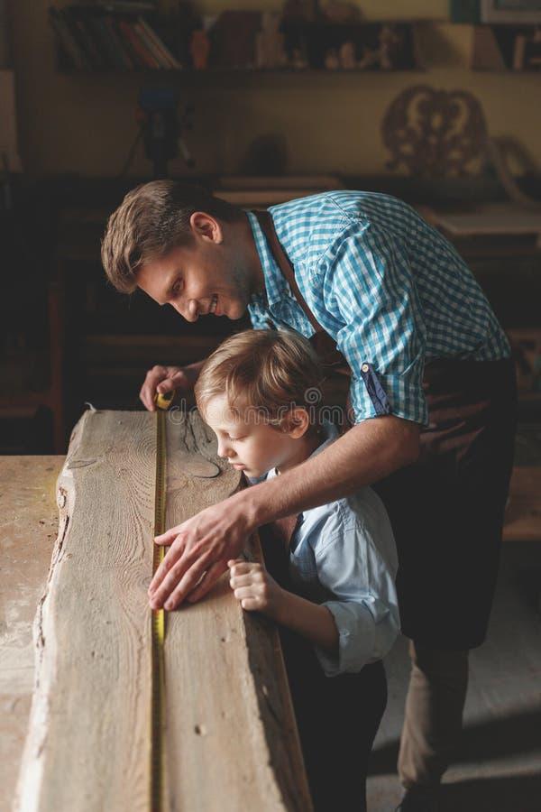 Le fadern och sonen som mäter ett bräde royaltyfri fotografi