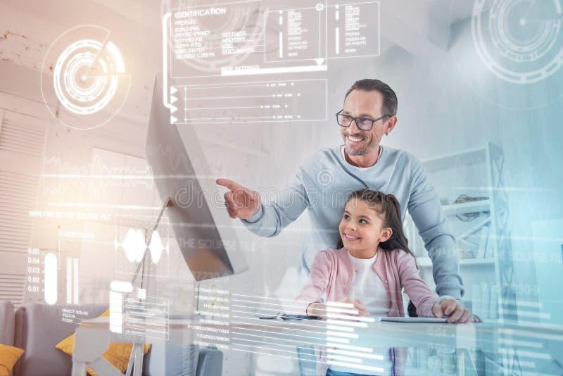 Le fadern som pekar till skärmen, medan göra läxa med hans dotter royaltyfri foto