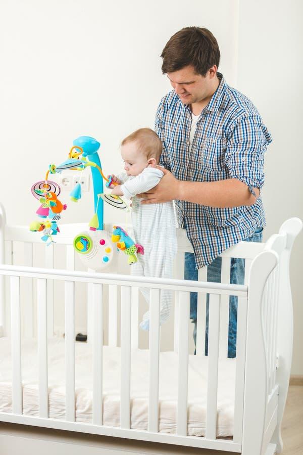 Le fadern som rymmer hans gulligt, behandla som ett barn i kåta på barnkammaren royaltyfri foto