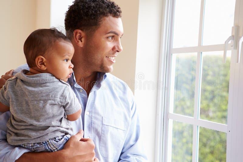 Le fadern Standing By Window med behandla som ett barn sonen hemma royaltyfria foton