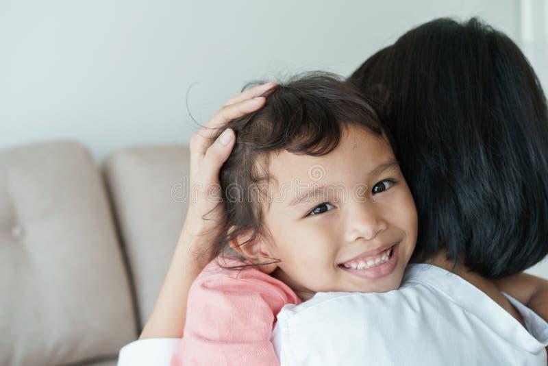 Le famiglie asiatiche con i derivati e le madri stanno abbracciando con amore La ragazza asiatica con un sorriso sul suo fronte è immagini stock