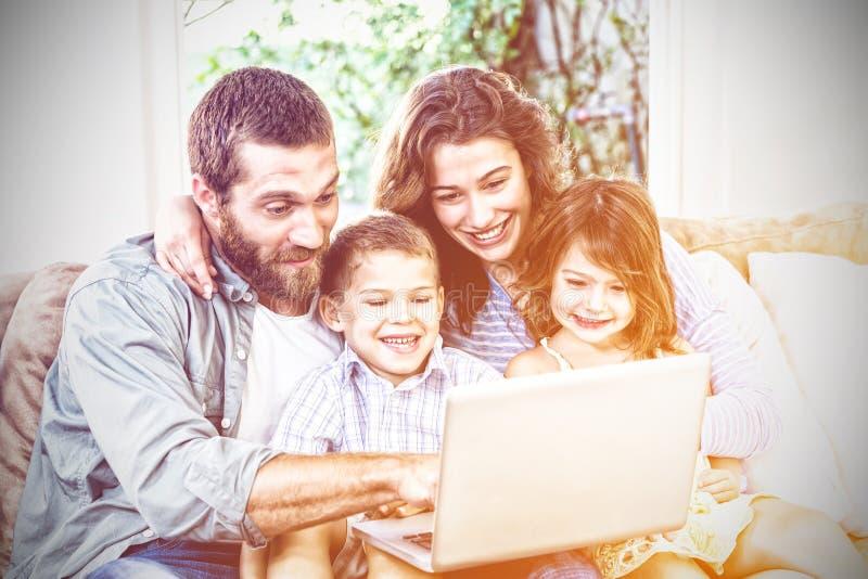 Le familjen med bärbara datorn royaltyfri fotografi