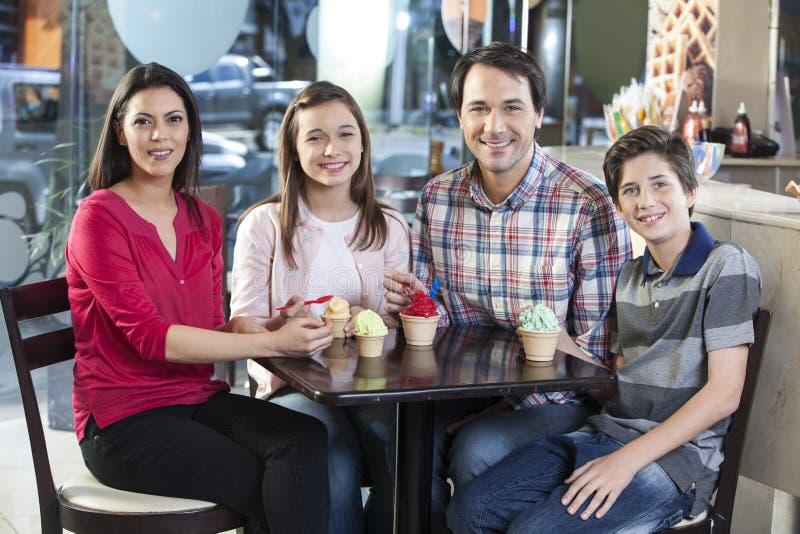 Le familjen med glassar på tabellen i mottagningsrum arkivfoton