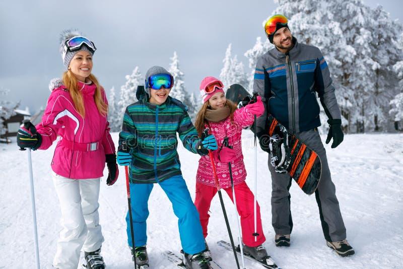 Le familjen med skida, och snowboarden skidar på ferie i berg arkivbilder