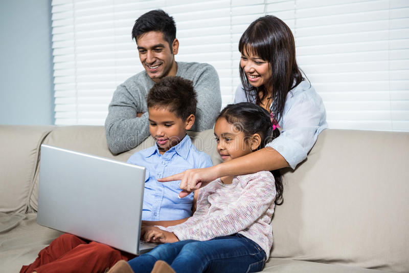 Le familjen som använder bärbara datorn på soffan royaltyfri fotografi