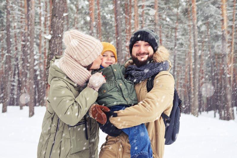 Le familjen som kramar sonen och att se kameran under snowf fotografering för bildbyråer