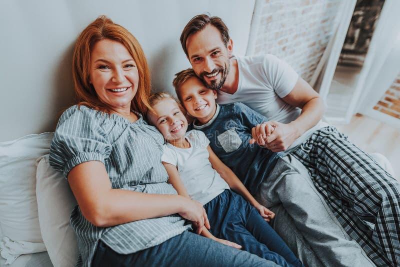 Le familjen som tillsammans lägger på säng i morgon royaltyfri foto