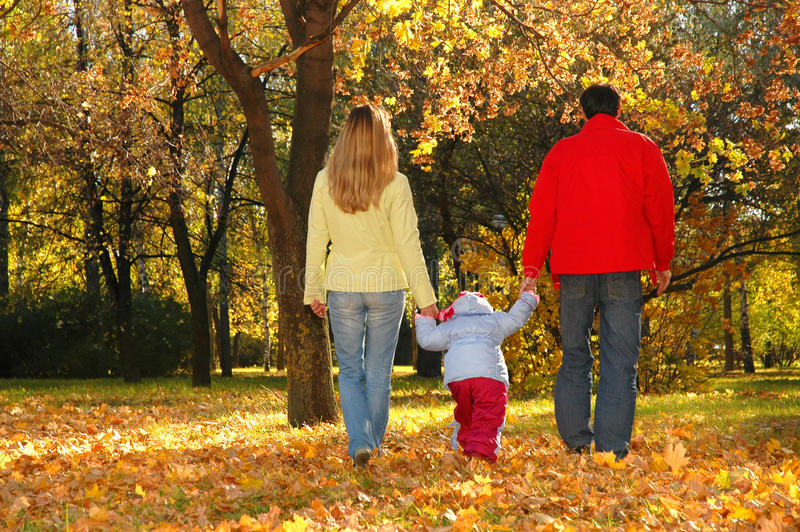 Le famille avec l'enfant entrent en stationnement d'automne photographie stock libre de droits