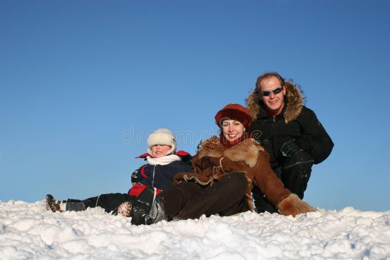 Le famille de l'hiver s'asseyent sur la neige images stock