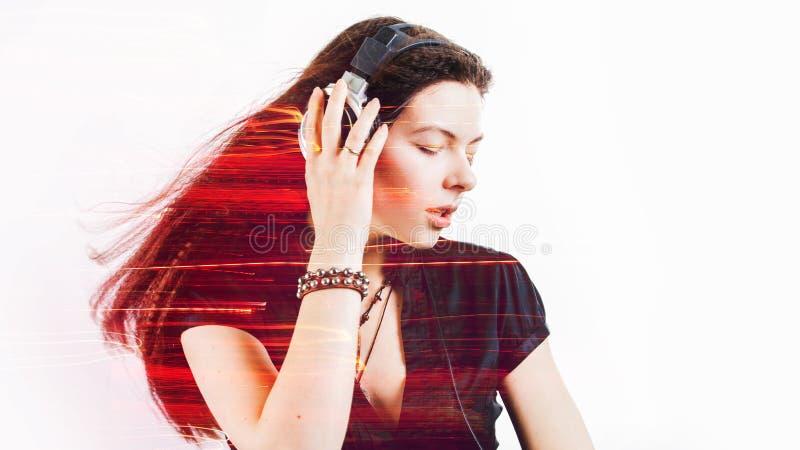 Le fan de fille chante et danse ?couter la musique La jeune femme de brune dans de grands ?couteurs appr?cie la musique images libres de droits