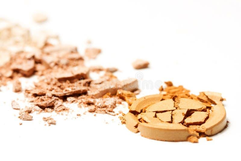 Le fard à paupières beige d'or a écrasé le cosmétique d'isolement sur le fond blanc Beauté, mode et style photographie stock libre de droits