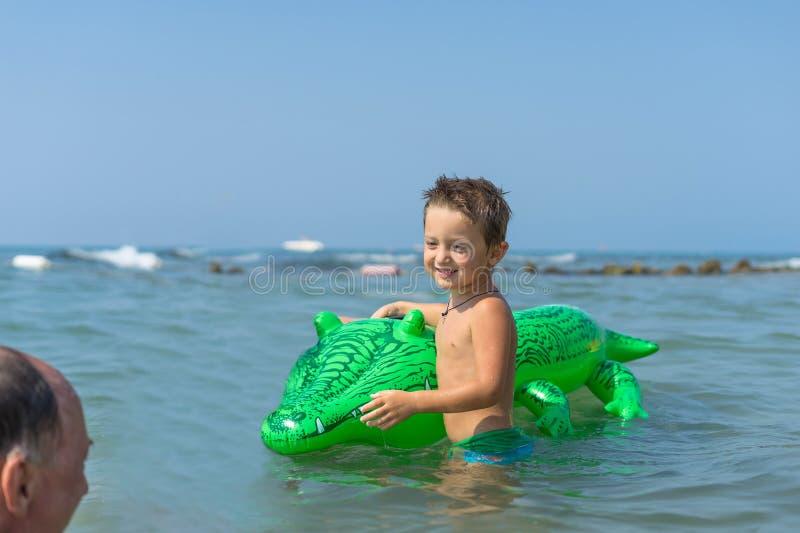 Le farfadern och sonsonen som spelar och plaskar i havsvattnet Stående av den lyckliga pojken för liten unge på stranden av havet royaltyfria foton