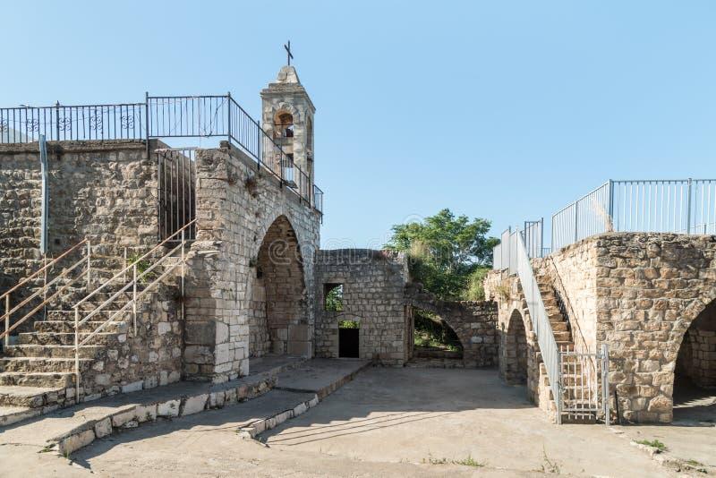 Le fasade avec le beffroi de l'église de fonctionnement de Christian Maronites dans le village abandonné Kafr Birim dans le nord  image libre de droits