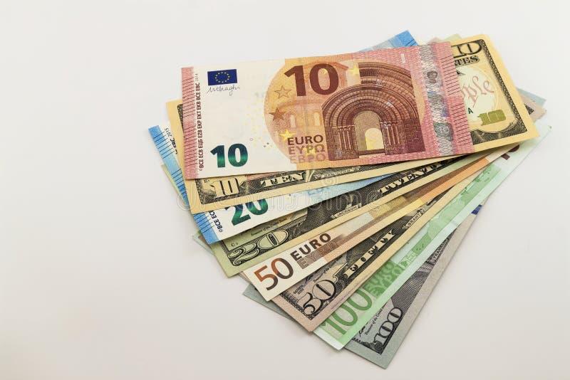 Le fatture di dollaro americano e le euro fatture hanno sparso misto su fondo bianco fotografie stock
