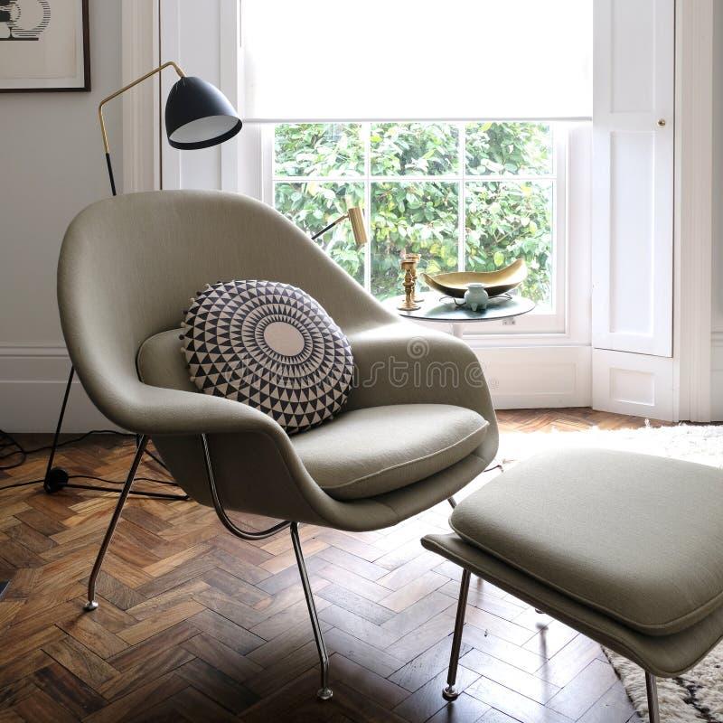 Le fauteuil vert clair confortable par la fenêtre dans la lumière a rempli pièce images stock