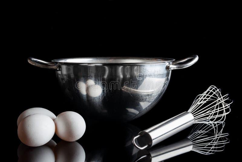 Le favori en acier de cuvette eggs du côté sur le noir photographie stock libre de droits
