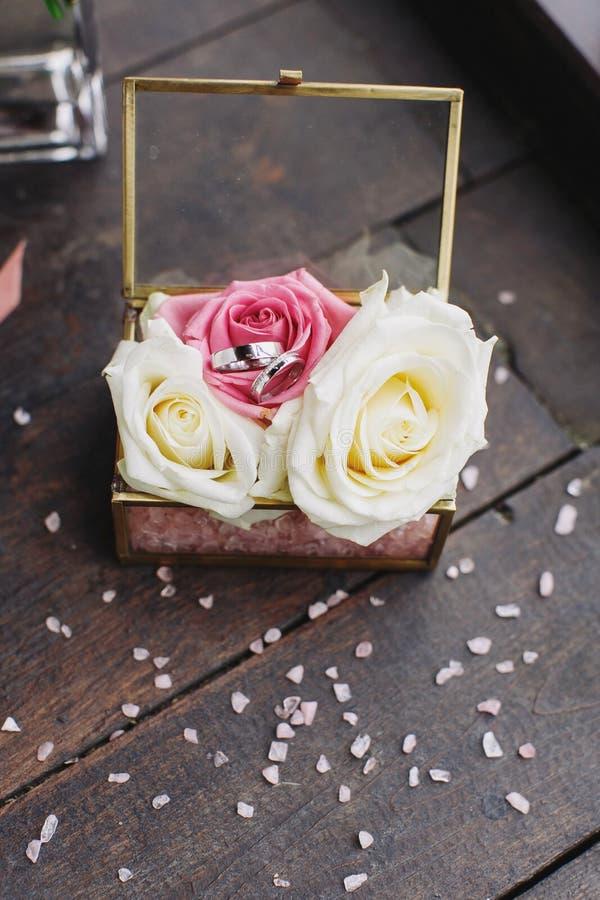 Le fedi nuziali della sposa e dello sposo sono in una scatola di vetro sulle rose, la scatola è sulla tavola di legno nella stanz fotografie stock