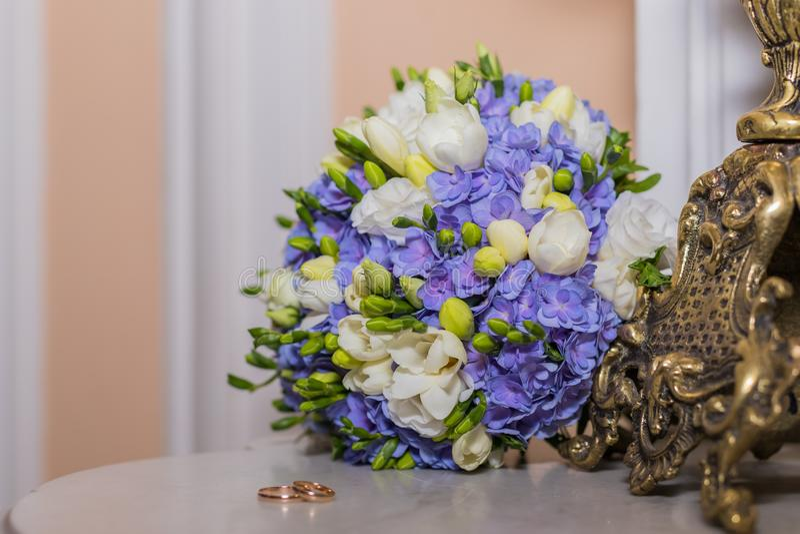 Le fedi nuziali si trovano e bello mazzo come accessori nuziali Due anelli e fiori dorati di nozze Cartolina d'auguri immagini stock