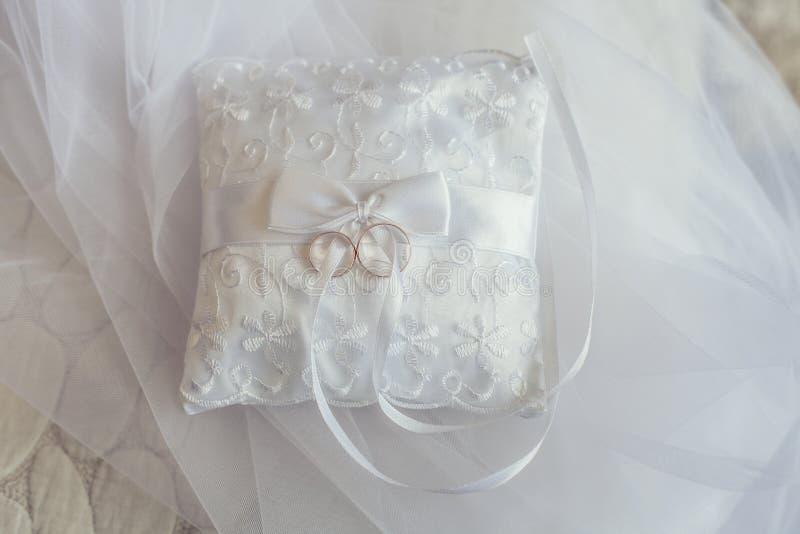 Le fedi nuziali si trovano su un bello cuscino bianco di nozze fotografia stock libera da diritti