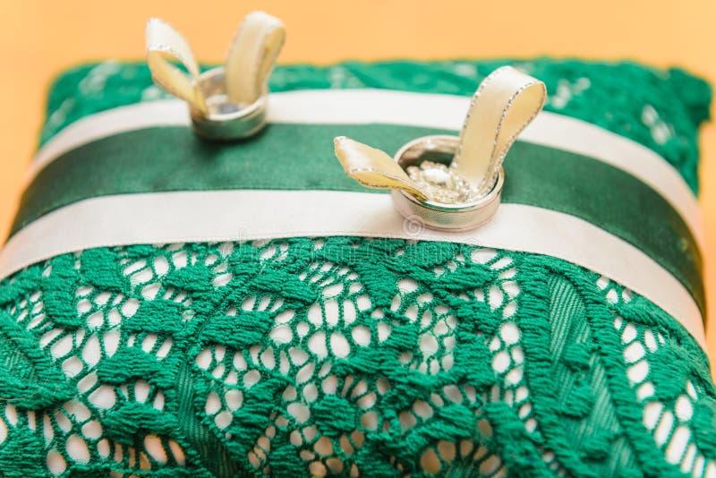 Le fedi nuziali si trovano su un cuscino bianco e di verde immagine stock libera da diritti