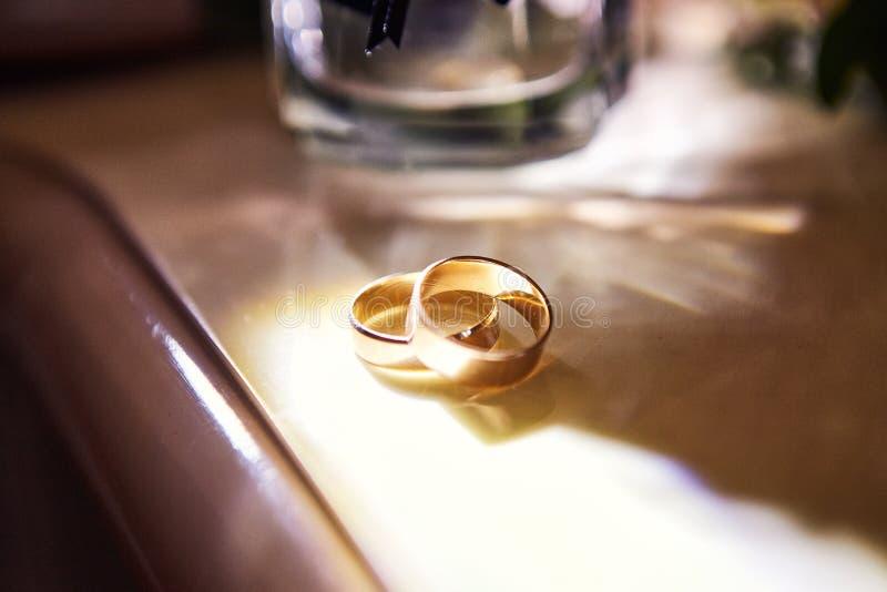 Le fedi nuziali si trovano sulla tavola vicino ad un mazzo di nozze fotografie stock