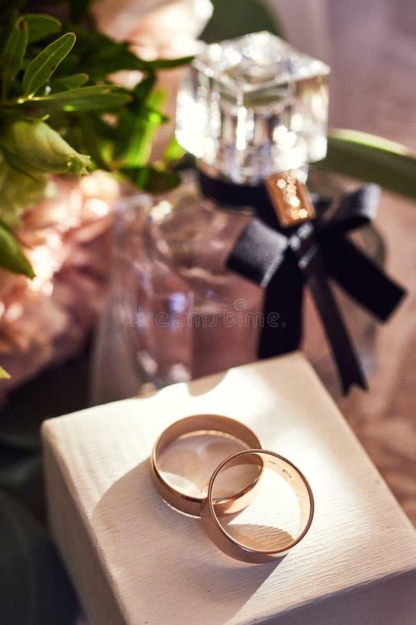 Le fedi nuziali si trovano sulla tavola vicino ad un mazzo di nozze fotografia stock libera da diritti