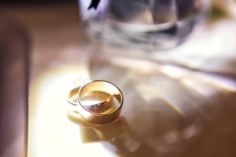 Le fedi nuziali si trovano sulla tavola vicino ad un mazzo di nozze immagini stock