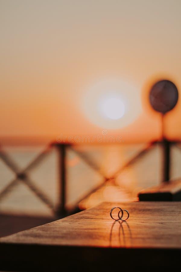 Le fedi nuziali su una bella struttura di legno sorgono contro il sole del tramonto immagine stock libera da diritti