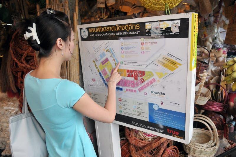 Le femme étudie une carte au marché de Chatuchak à Bangkok image libre de droits